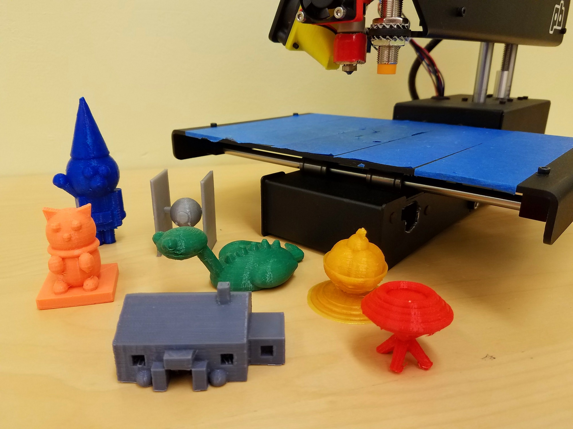 a colorful assortment of small 3D-printed figures arranged in front of a 3D printer