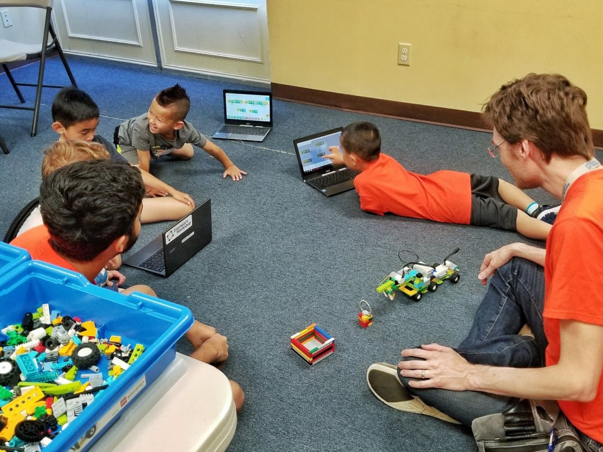 children with laptops sit or lay on the floor with a six-wheeled LEGO robot performing a complex task