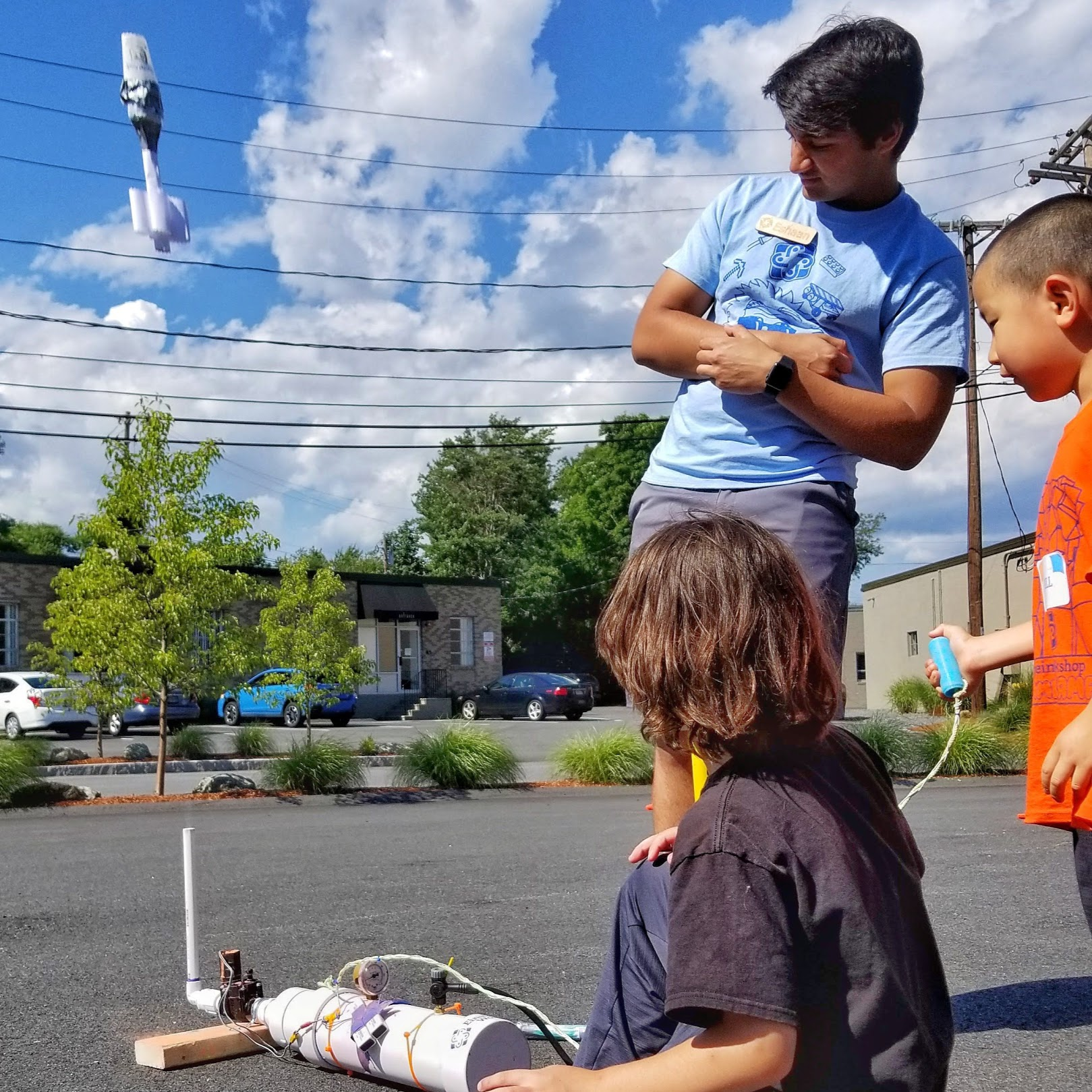 student launching rocket out of compressed air launcher while mentor and another student watch