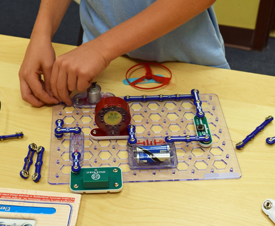 Picture of child's hands assembling snap circuit