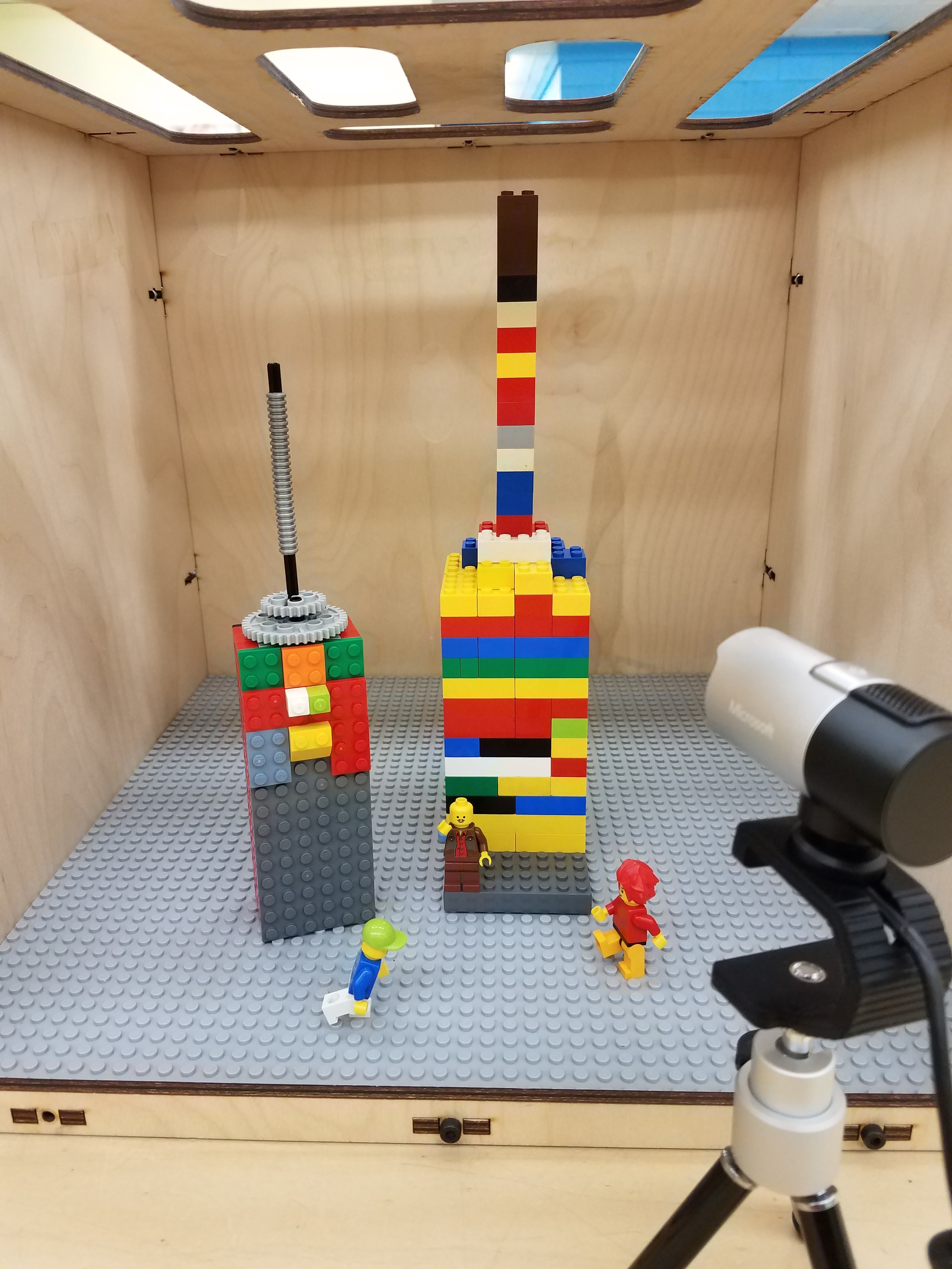 picture of a well-lit LEGO scene inside a wooden box, with a camera on a tripod in the foreground capturing the scene